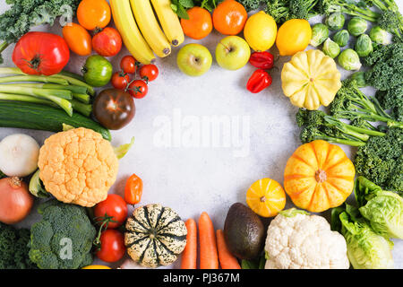 Assorted colorful vegetables and fruits arranged in a circle on the light grey background, copy space for text in the middle, selective focus - Stock Photo