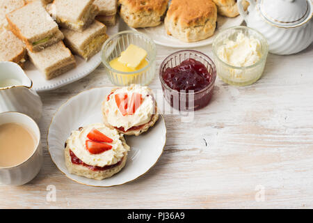 Cream teas, scones with jam and cream, tea with milk, with sandwiches on the back, on the white wooden table, selective focus copy space for text - Stock Photo