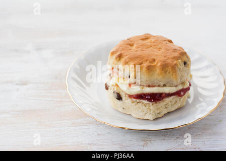 One scone with jam and cream, on the plate, on the white wooden table, selective focus, close up, copy space for text - Stock Photo