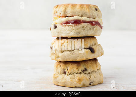 Three scones in a stack with jam and cream, on the plate, on the white wooden table, selective focus copy space for text - Stock Photo