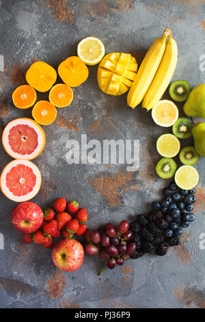 Rainbow colored fruits in a circle, strawberries, blueberries, mango, orange, grapefruit, banana, apple, grapes, kiwis, papaya on the grey background, - Stock Photo
