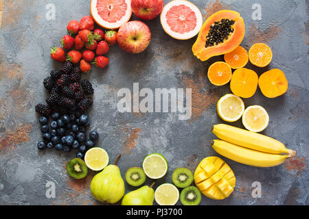 Rainbow color fruits arranged in a circle, strawberries, blueberries, mango, orange, grapefruit, banana, apple, grapes, kiwis, papaya on the grey back - Stock Photo