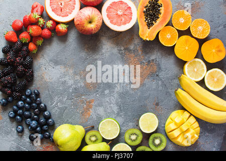Rainbow colored fruits and berries arranged in a circle, on the grey stone background, copy space for text, selective focus - Stock Photo