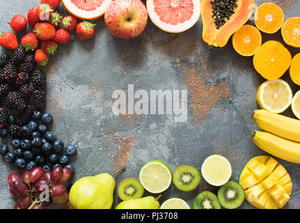 DIfferent rainbow colored fruits and berries arranged in a circle, on the grey stone background, copy space for text, selective focus - Stock Photo
