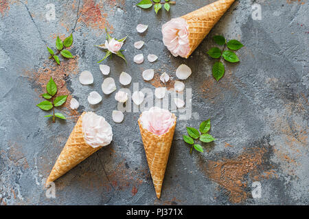 Top view of ice cream cones with roses, overhead composition with flowers, petals, leaves on the grey stone background, copy space for text - Stock Photo