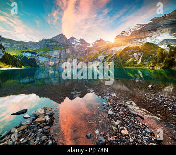Colorful summer morning on unique lake - Oeschinen (Oeschinensee), UNESCO World Heritage Site. Switzerland, Europe. - Stock Photo