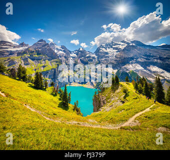 Colorful summer morning on unique lake - Oeschinen (Oeschinensee), UNESCO World Heritage Site. Switzerland, Europe. - Stock Photo