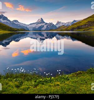 Wetterhorn peak reflected in water surface of Bachsee lake. Colorful summer sunrise in Bernese Oberland Alps, Innertkirchen, Switzerland - Stock Photo