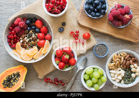 Paleo style breakfast, grain free granola made with nuts and dried fruits, served with fresh berries, top view, selective focus - Stock Photo