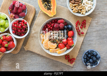 Above view of paleo style breakfast, grain free granola made with nuts and dried fruits, served with fresh berries, selective focus - Stock Photo