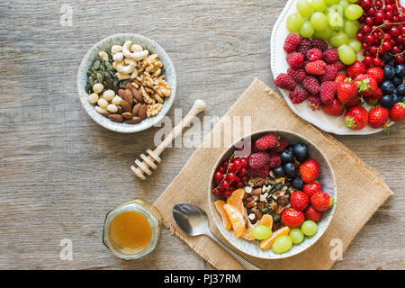 Paleo style breakfast, grain free muesli made with nuts and dried fruits, served with fresh berries, top view, selective focus - Stock Photo