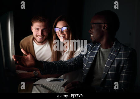 employees discussing something sitting at the Desk - Stock Photo
