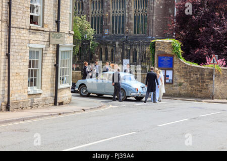 The Bride and Bridesmaids and wedding party enter the church of St Mary the Virgin and St Mary Magdalen, Tetbury, Gloucestershire, for a summer wedding - Stock Photo