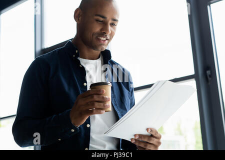 Successful African entrepreneur studying documents with attentive and concentrated look, drinking coffee at cafe. Dark-skinned businessman focused on work issues, signing papers for business deals - Stock Photo
