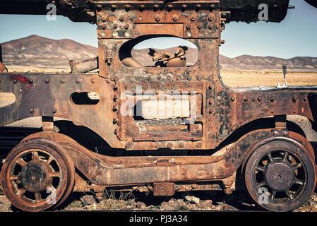 Wheel of an old rusty wagon abandoned in the train cemetery of Uyuni, Bolivia - Stock Photo