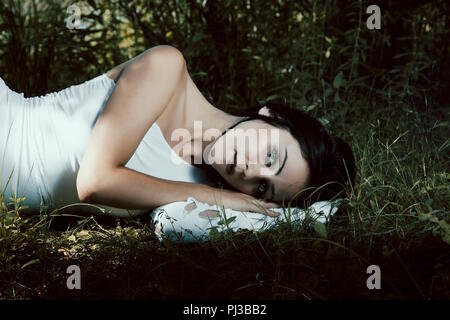 Pale woman in white dress lying on the ground, fairytale scene - Stock Photo
