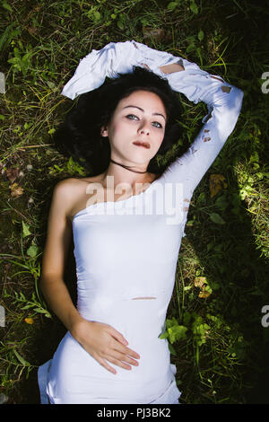 Pale woman in white dress on the ground, dark mystery scene - Stock Photo