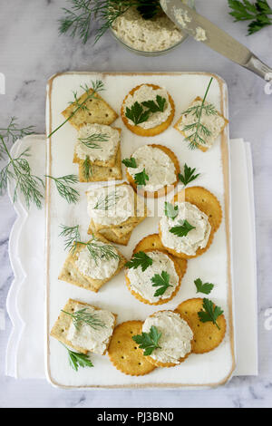 Snack from crackers and curd fish paste with herbs on a light background. Selective focus. - Stock Photo