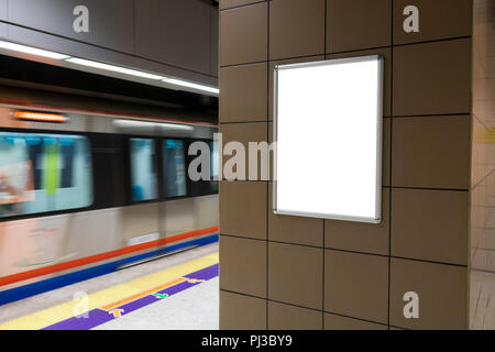 One big vertical / portrait orientation blank billboard in public transport with subway platform background