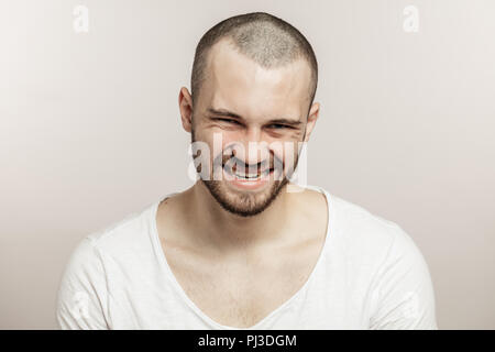 Close-up portrait a funny bearded man making crazy face - Stock Photo