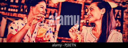 Two young women having cocktail drinks - Stock Photo