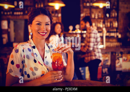 Portrait of young woman having cocktail drink - Stock Photo