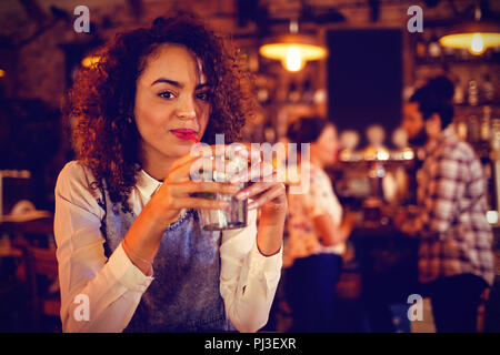 Portrait of young woman having a cocktail drink - Stock Photo