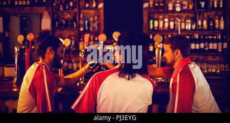 Group of male friends toasting beer bottles - Stock Photo