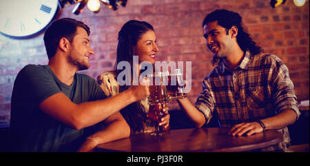 Young friends toasting beer mugs - Stock Photo