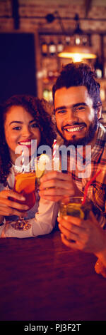 Portrait of young friends having drinks - Stock Photo
