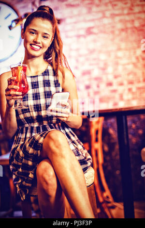 Portrait of two young women having cocktail drinks - Stock Photo