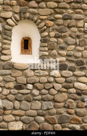 Old stone wall made with irregular blocks and window background texture. - Stock Photo
