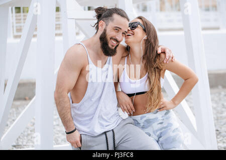 young couple listening music with earphones while relaxing on pebble beach - Stock Photo
