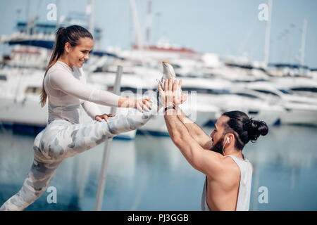 Male coach helping young woman exercising on pier. - Stock Photo