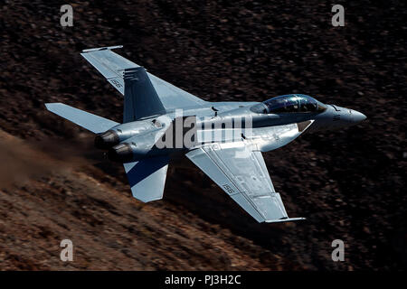 United States Navy Boeing F/A-18F Super Hornet (side 156) from the  VFA-122 Flying Eagles squadron flies low level on the Jedi Transition through Star Wars Canyon / Rainbow Canyon, Death Valley National Park, Panamint Springs, California, United States of America - Stock Photo