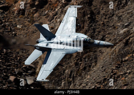 United States Navy Boeing F/A-18F Super Hornet (side 104) from the VFA-154 Black Knights squadron flies low level on the Jedi Transition through Star Wars Canyon / Rainbow Canyon, Death Valley National Park, Panamint Springs, California, United States of America - Stock Photo