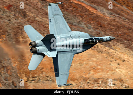 United States Navy Boeing F/A-18F Super Hornet (side 102) from the VFA-154 Black Knights squadron flies low level on the Jedi Transition through Star Wars Canyon / Rainbow Canyon, Death Valley National Park, Panamint Springs, California, United States of America - Stock Photo