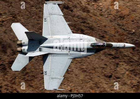 United States Navy Boeing F/A-18E Super Hornet (side 313) from the VFA-146 Blue Diamonds squadron flies low level on the Jedi Transition through Star Wars Canyon / Rainbow Canyon, Death Valley National Park, Panamint Springs, California, United States of America - Stock Photo
