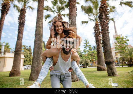 Playful sportive men giving piggyback ride to women at tropical park - Stock Photo