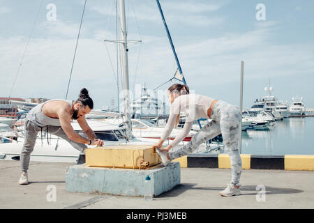 Young beautiful couple doing stretching exercises at the ocean pier - Stock Photo