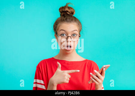 is it your phone emotional amazed woman indicates at phone - Stock Photo