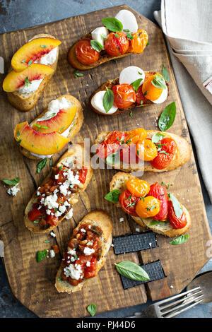 Crostini or bruschetta board with caprese, tomatoes, eggplant caponata and peaches - Stock Photo