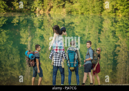crazy girl is resting on the shoulders of friend as she has tired to go hiking - Stock Photo