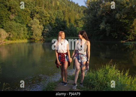 two positive hipster girls are resting on the wonderful landscape - Stock Photo