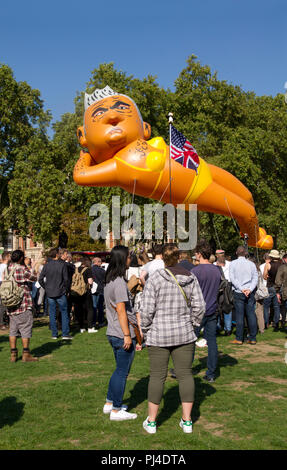 A giant balloon depicting the current London Mayor Sadiq Khan wearing a bright yellow bikini being flown over the Houses of Parliament in Westminster. - Stock Photo