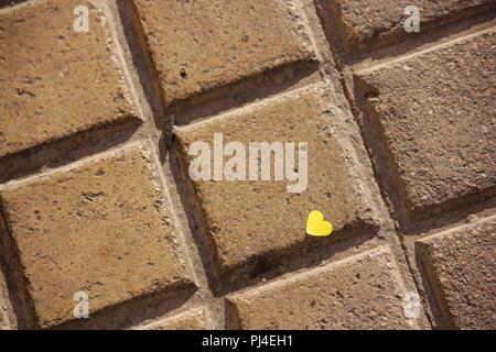 A yellow heart on the brickwork floor - Stock Photo