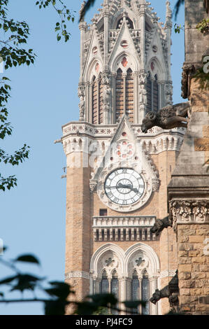 A carved ram or sheep and dog on the Mumbai University building, superimposed against Rajabai clock tower - Stock Photo