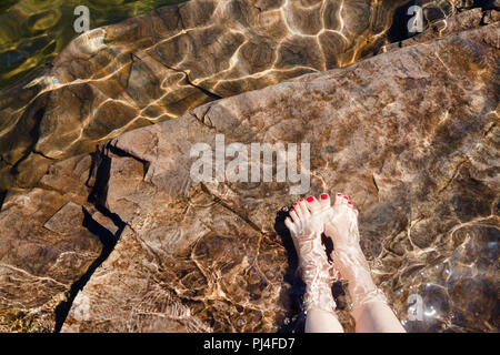 Young woman dipping her feet in a crystal clear water of a lake or fjord in Norway - Stock Photo