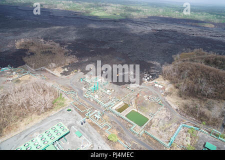 Aerial view of Puna Geothermal Ventures which was encroached upon by lava from the recent three month eruption in Leilani Estates on Hawaii Island. The Hawaii Army National Guard provided key leadership from the Hawaii County, FEMA, USGS, and the Hawaii National Guard with an aerial survey of areas of the island effected by the recent eruption and hurricane Lane. August 29 2018, Hilo Hawaii. (U.S Air National Guard Photo by Tech. Sgt. Andrew Jackson) - Stock Photo