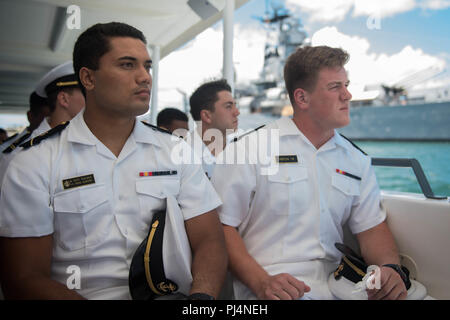 180831-N-AV243-0001 PEARL HARBOR (August 31, 2018) U.S. Navy Midshipmen, Pepe Tanuvasa (left) and Taylor Heflin linebackers for the U.S. Naval Academy football team, reflect on the lives lost on December 7th, 1941 during a Pearl Harbor memorial boat tour.  The U.S. Navy Midshipmen visited the Pearl Harbor visitor center the day prior to their game against University of Hawaii's Rainbow Warriors on September 1, 2018. (U.S. Navy photo by Mass Communication Specialist 2nd Class Somers T. Steelman.) - Stock Photo